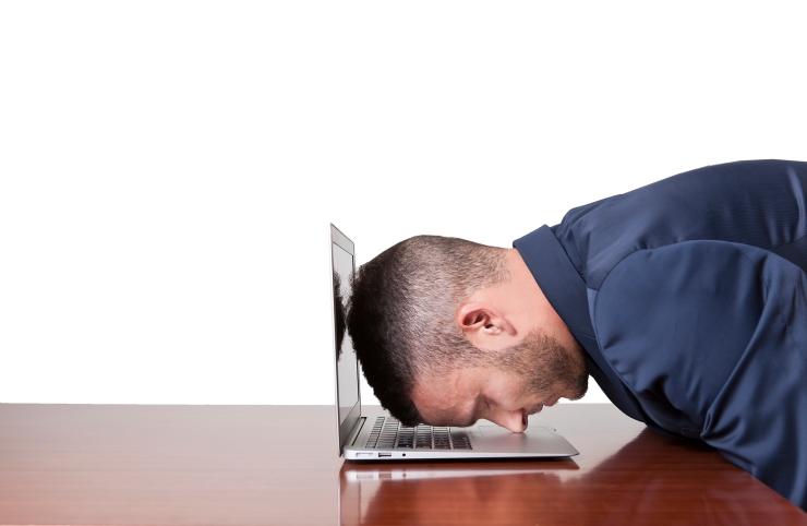 Stressed businessman sleep with head on laptop